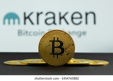 The coins of bitcoin are in front of logo of Kraken crypto stock exchange background. In the foreground is a BTC coins and on the background is a white Kraken cryptocurrency market emblem. Los Angeles