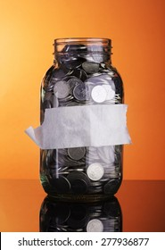 Coins in bottle with empty label for text - financial concept