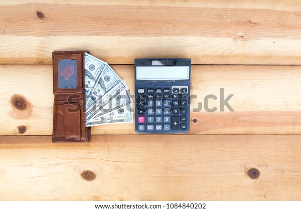Coins and the calculator on wood background