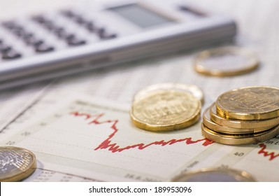 Coins, chart and calculator as a symbol for exchange rates.