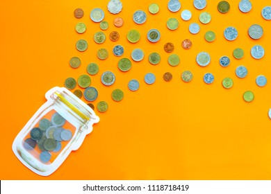 coins in different  currencies flow into the piggy bank in jar pattern on orange background