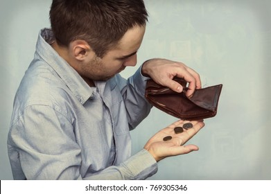 Coins and an empty wallet. poor man pulls out the last coins from her purse