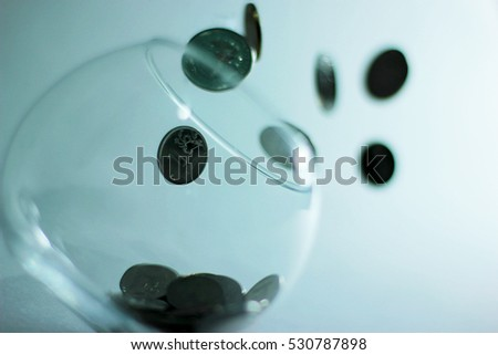 coins falling into the clear jar