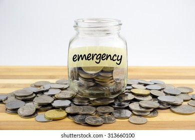 Coins in glass container with EMERGENCY label on wooden surface against white background.Financial concept.Selective focus.