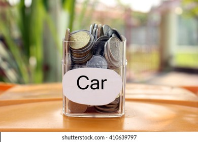 Coins in a glass container with a label car . Financial concept.