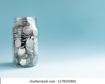Coins in glass jar isolated on blue background with copy space. Saving money concept.