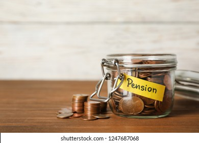 """Coins in glass jar with label """"PENSION"""" on table against light wall. Space for text"""
