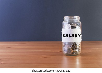 Coins in a glass jar labeled with SALARY label. Financial and salary conceptual.