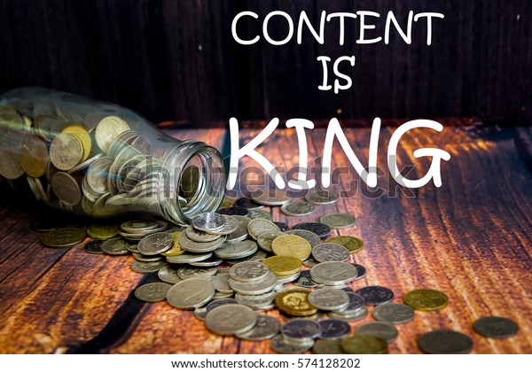 """Coins in glass jar for money saving financial and business concept with wording """"CONTENT IS KING"""""""