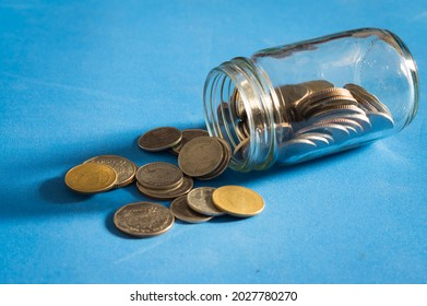 Coins with glass jar on blue table.