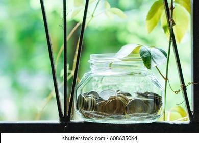 Coins in glass jar on green nature background - Vintage Filter