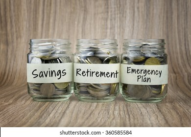 Coins in glass jar with saving, retirement and emergency plan label. Financial Concept