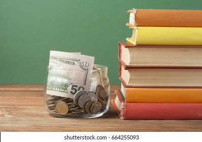 Coins in glass jar and stack of books on wooden table.Concept of funding education.
