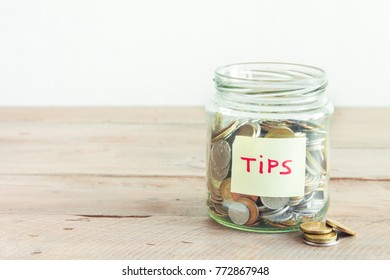 Coins in glass jar with Tips label. Money savings, tips and donation concept, copy space.