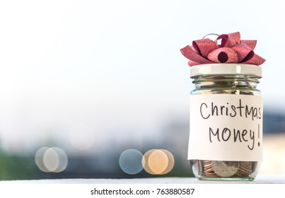Coins in glass jar with the word Christmas money saving with bokeh background