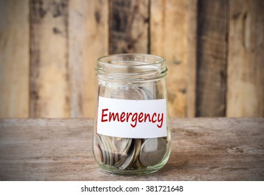 Coins in glass money jar with emergency label, financial concept. Vintage wooden background