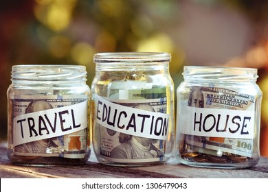 A lot coins in glass money jar on the wood table. Saving for house, travel and educatiuon