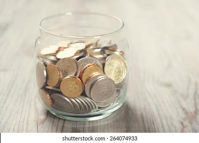 Coins in glass money jar, on wooden background.