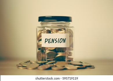 A lot coins in glass money jar on the table. Financial Pension Concept.