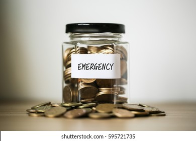 A lot coins in glass money jar on the table. Saving for emergency concept.