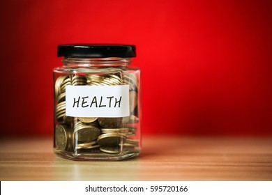 A lot coins in glass money jar with red background. Saving for Health concept.