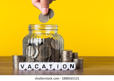 A lot coins in glass money jar with yellow background. Saving for Vacation concept.