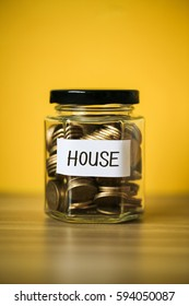 A lot coins in glass money jar with yellow background. Saving for house concept.
