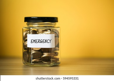 A lot coins in glass money jar with yellow background. Saving for emergency concept.