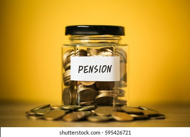 A lot coins in glass money jar with yellow background. Financial Pension Concept.