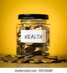 A lot coins in glass money jar with yellow background. Saving for Health concept.