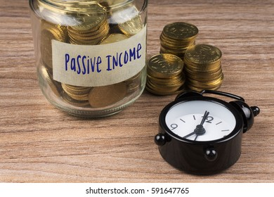 Coins in glass with Passive Income label on wooden background. Financial concept.