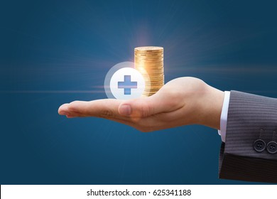 Coins in the hand of a businessman with a plus sign
