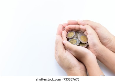 Coins in hands of daughter with mother's hands protection on white background