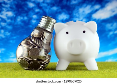 Coins inside the light bulb and piggy bank. Green eco renewable energy concept. Electricity prices, energy saving in the household.