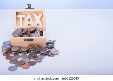 Coins inside a wooden box with TAX sign,taxation concept