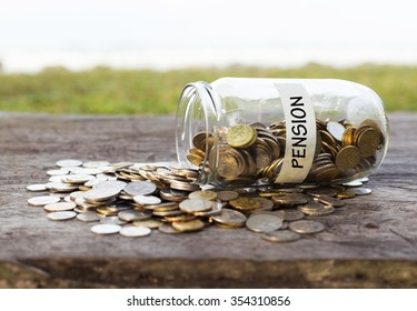 Coins in the jar or glass on the wood with PENSION label against bokeh beach background. Financial concept. Selective focus.