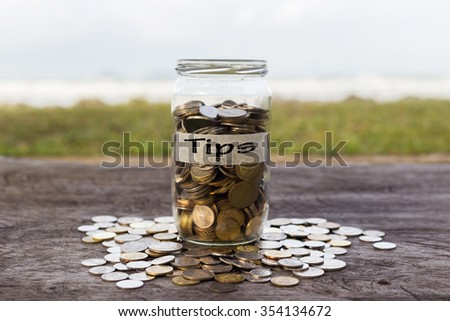 Coins in the jar or glass on the wood with TIPS label against bokeh beach background. Financial concept. selective focus