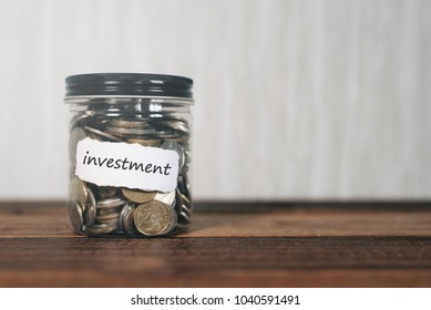 coins in a jar with label written INVESTMENT. financial concept