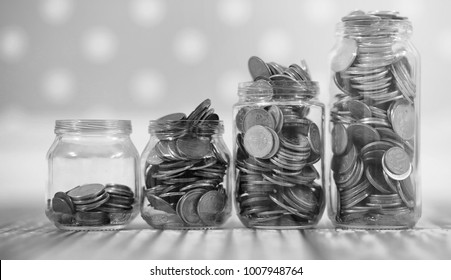 Coins in a jar on the floor. Accumulated coins on the floor. Pocket savings in piles.