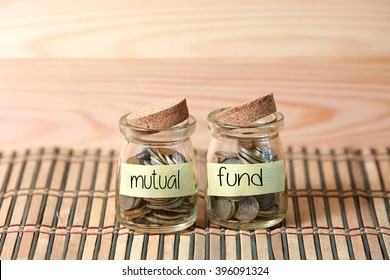 Coins in jar. Writing Mutual Fund on two jar with wooden pallet background. Selective focus with shallow depth of field.
