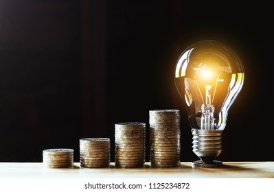 Coins and light bulb with hand putting to the lighting on wooden for saving money,energy concept in dark background.