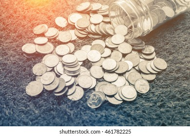 Coins in money jar on grass background with filter effect retro vintage style business saving concept