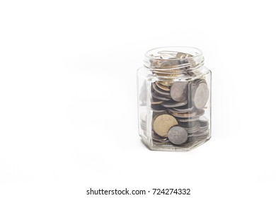 coins in a money jar over white background