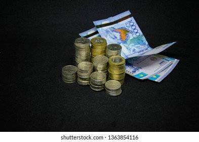 Coins on a dark background. Coins Kazakhstan tenge on a dark background. Kazakh money. Coins of tenge. large pile of coins and tenge paper banknotes
