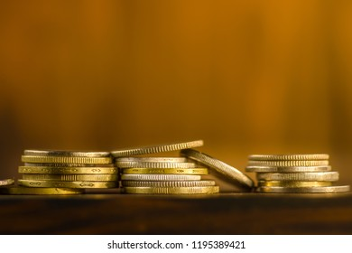 Coins on one another in a pile of on the table. Brown background