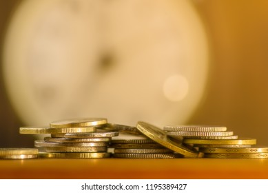 Coins on one another in a pile of on the table. Clock background
