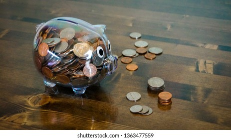 Coins on the table next to a nearly full clear piggy bank.
