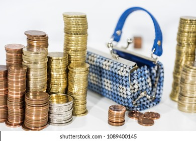 A lot of coins on white table with black purse. Abstract photo of money.