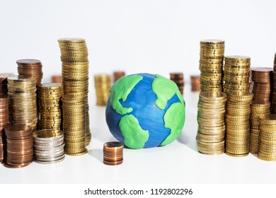 A lot of coins on white table with Earth model. Abstract photo of money.