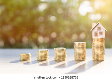 Coins on the wood and house in sunlight background present the savings money or investing to buy a home or loan. To buy a house or real estate or investment for the future.